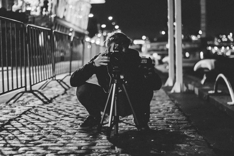 a photographer taking a low level shot with a camera on a tripod